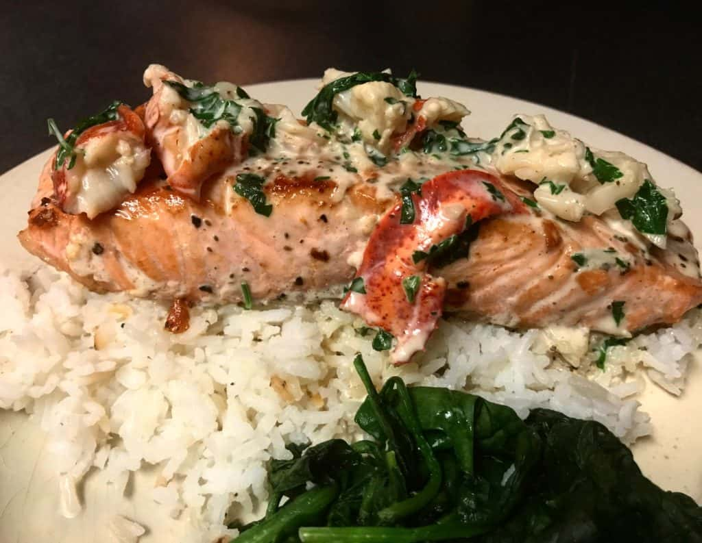 a plate of salmon with a lobster cream sauce