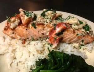 a plate of salmon with lobster cream sauce