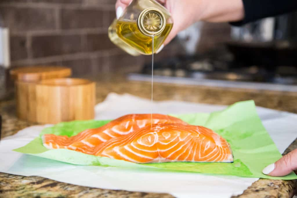 drizzling olive oil onto a piece of salmon