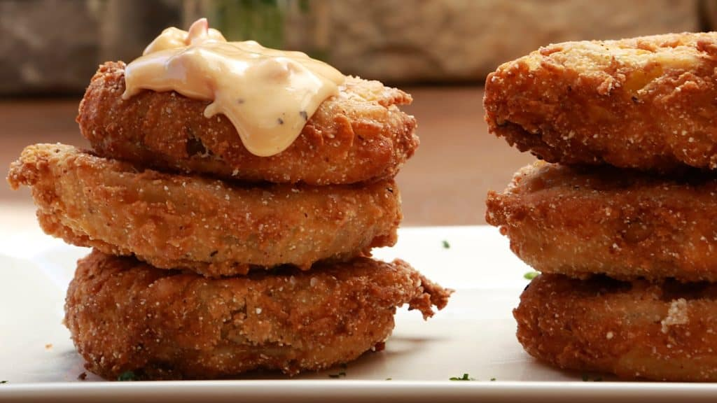 two stacks of three fried green tomato stacks topped with pimento cheese