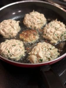 crab cakes frying in a non-stick pan