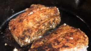 two blackened grouper filets in a cast iron pan
