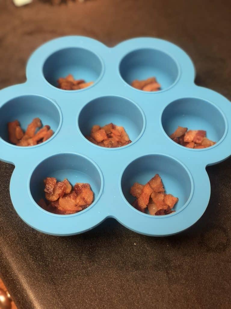 a blue sous vide egg bite mold filled with crisp bacon pieces