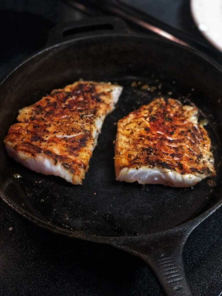 two filets of blackened grouper in a cast iron pan
