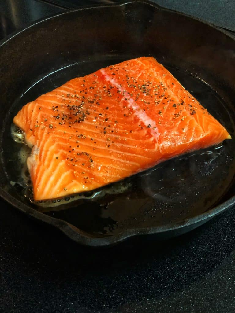 a filet of salmon in a cast iron pan