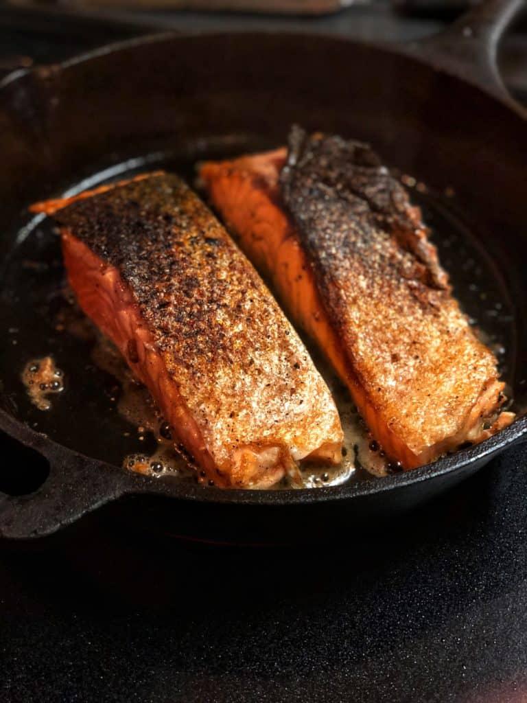 salmon searing in a cast iron pan