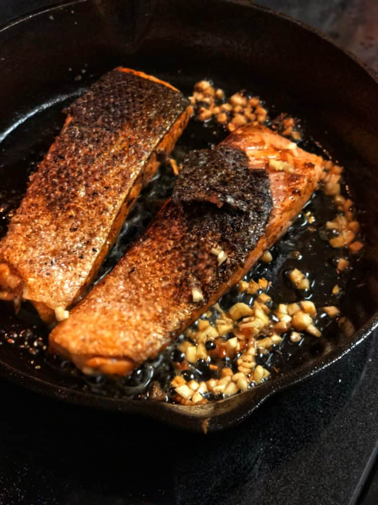 honey glazed salmon filets in a cast iron pan with garlic