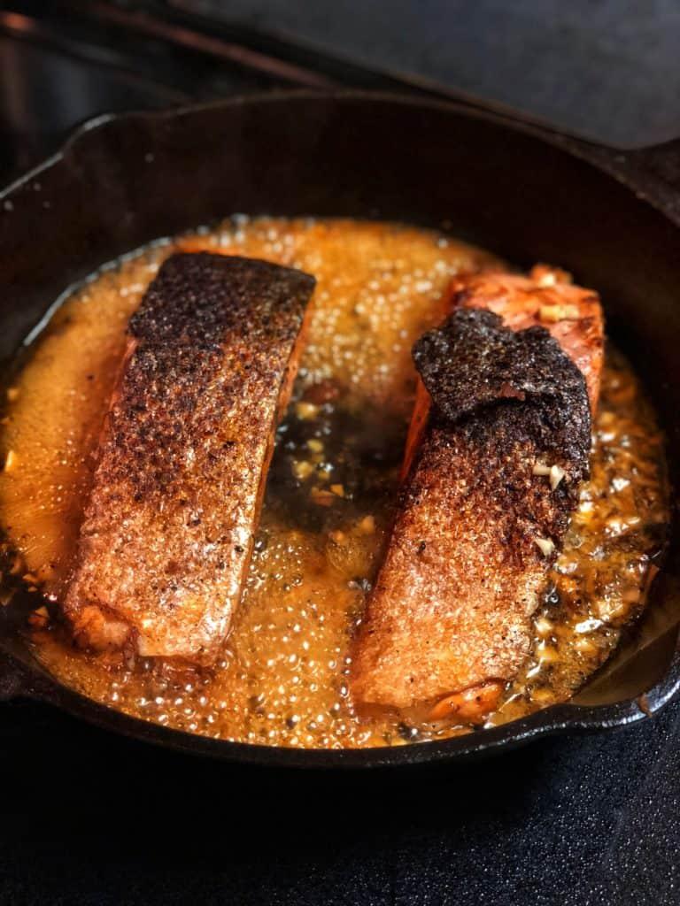 honey glazed salmon filets in a cast iron pan