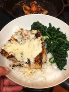 a white bowl with a piece of blackened group covered in my coconut lemon cream sauce for fish recipe