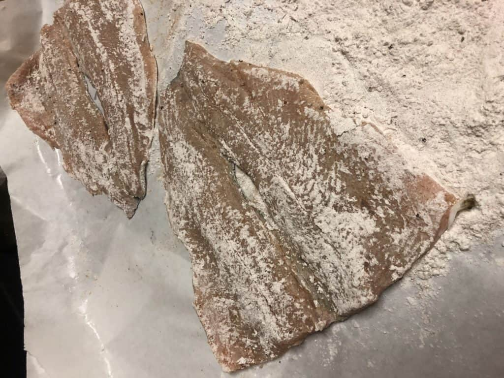 two pieces of trout dredged in flour