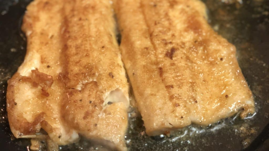 a filet of trout frying in a pan
