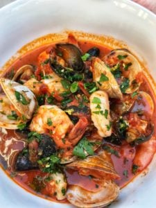 a white bowl of seafood stew - cioppino