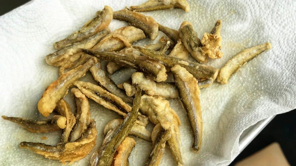 fried smelt fish on a paper towel