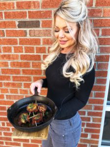 me holding a cast iron pan of bacon wrapped scallops
