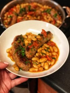 a white bowl of Italian sausage and beans