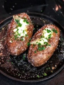 two baked potatoes on a flat cast iron pan