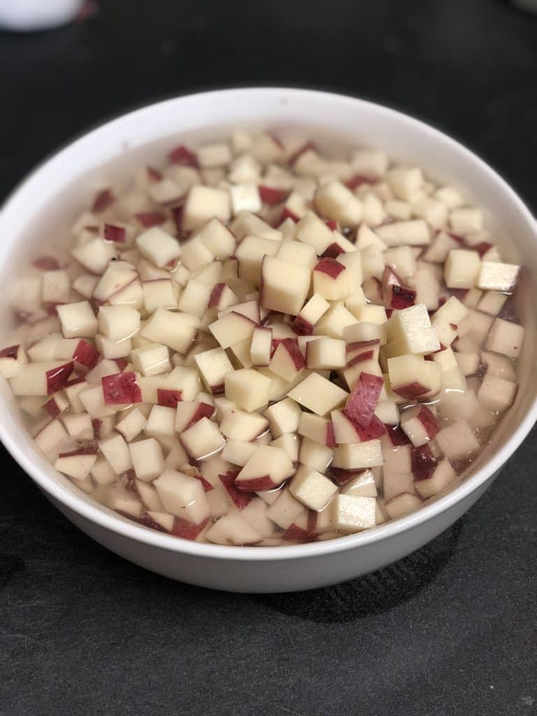a white bowl of diced potatoes