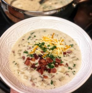 a white bowl of loaded baked potato soup