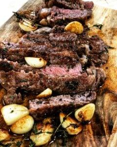 a steak cut up on a wooden board