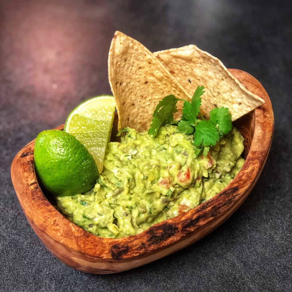 a wooden bowl of guacamole with limes and tortilla chips