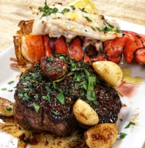 a filet and a lobster tail on a white plate