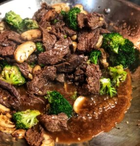 beef and broccoli in a wok