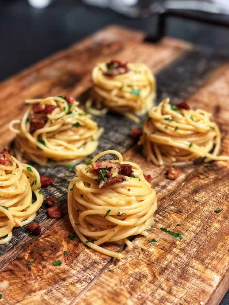 five mounds of pasta carbonara on a wooden board