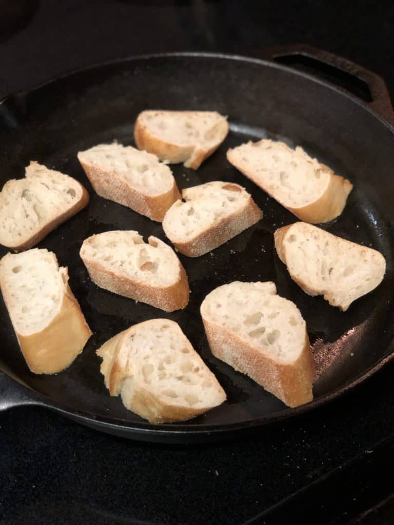 slices of bread in a cast iron pan for bruschetta