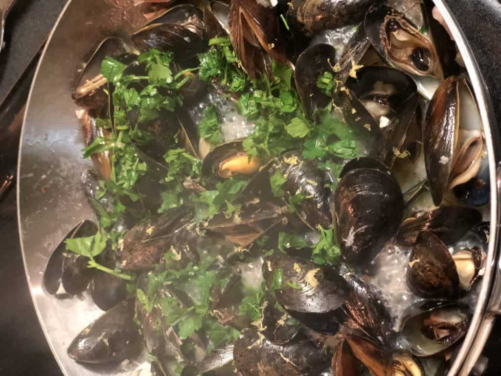 a pan of steamed mussels with white wine and garlic