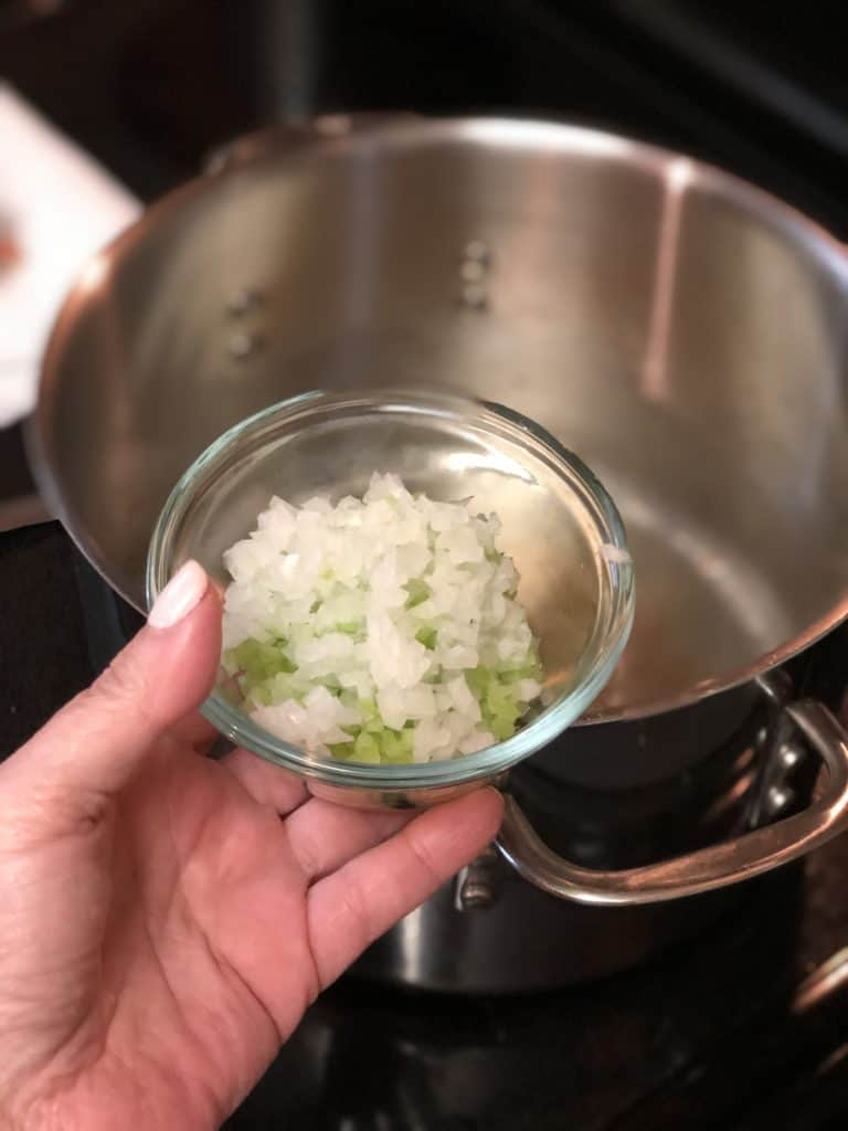 a glass bowl of celery and onions