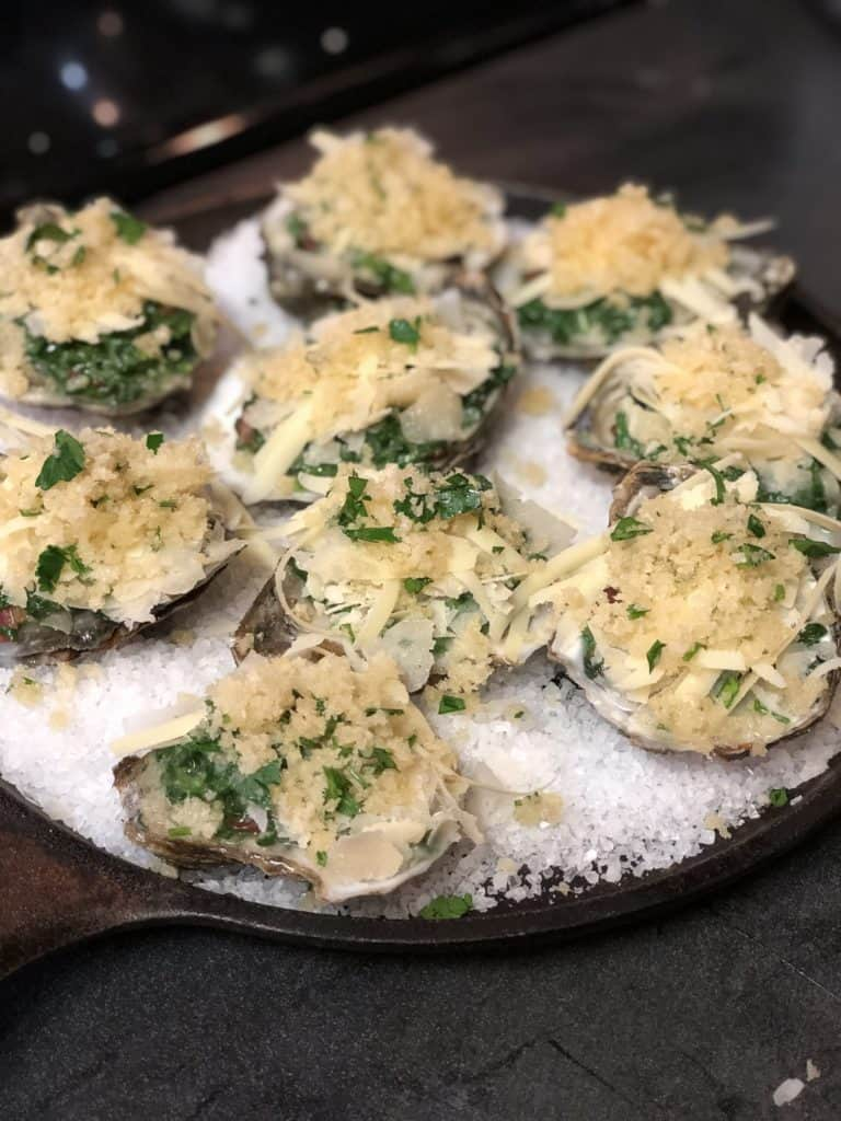 raw oysters topped with cheese and breadcrumb mixture