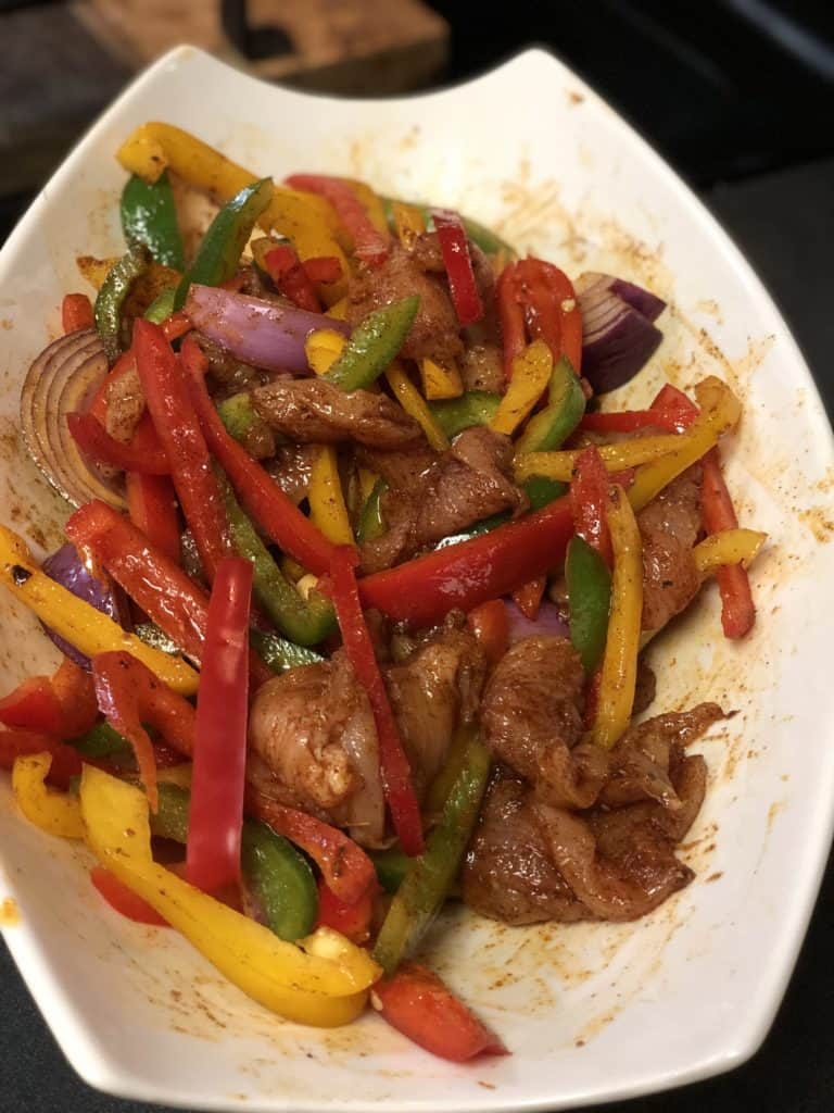 chicken and vegetables marinating in a white bowl
