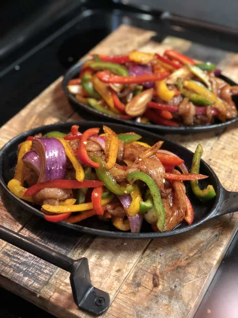 two cast iron pans filled with chicken fajitas