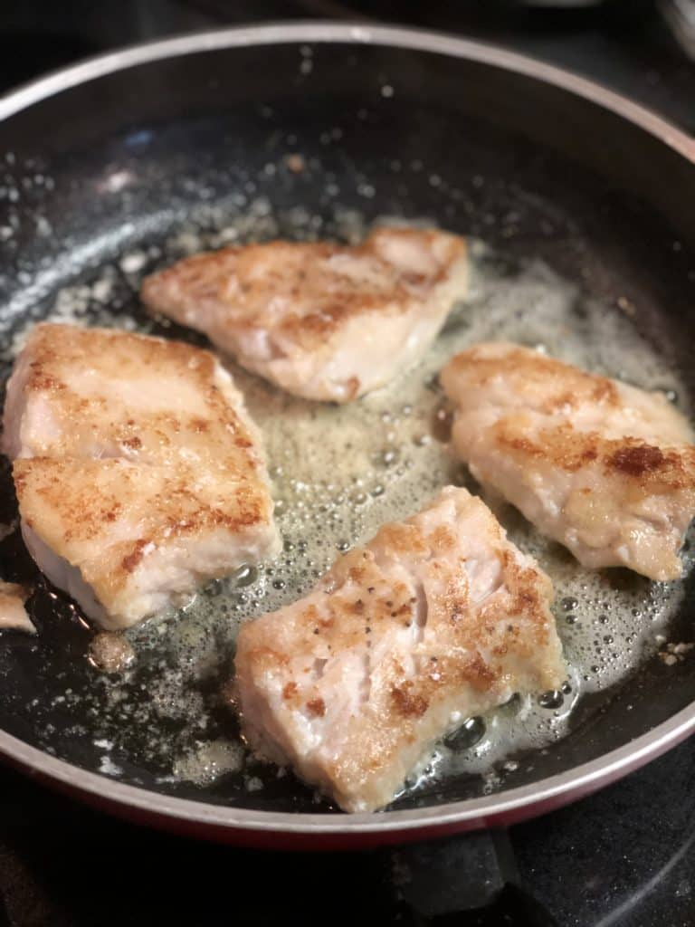 four grouper filets frying in a pan for grouper piccata