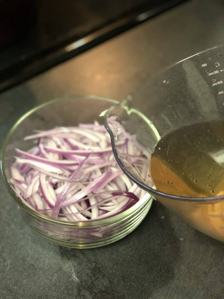 a glass bowl of red onions