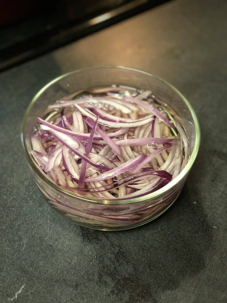 a glass bowl of pickled red onions