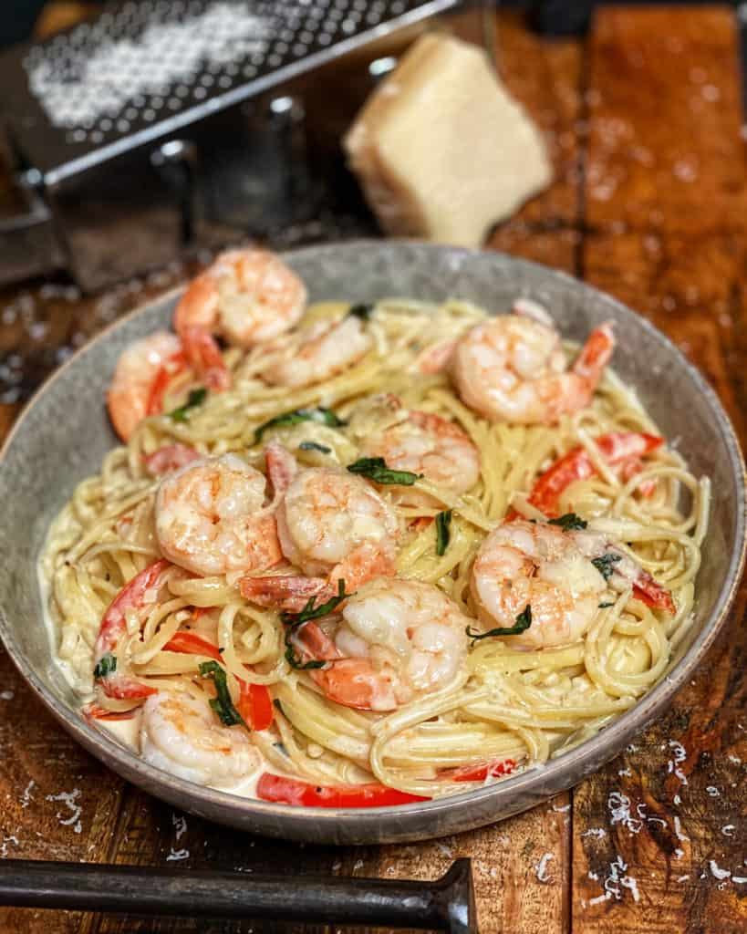 a bowl of fettuccine with shrimp in a cayenne cream sauce