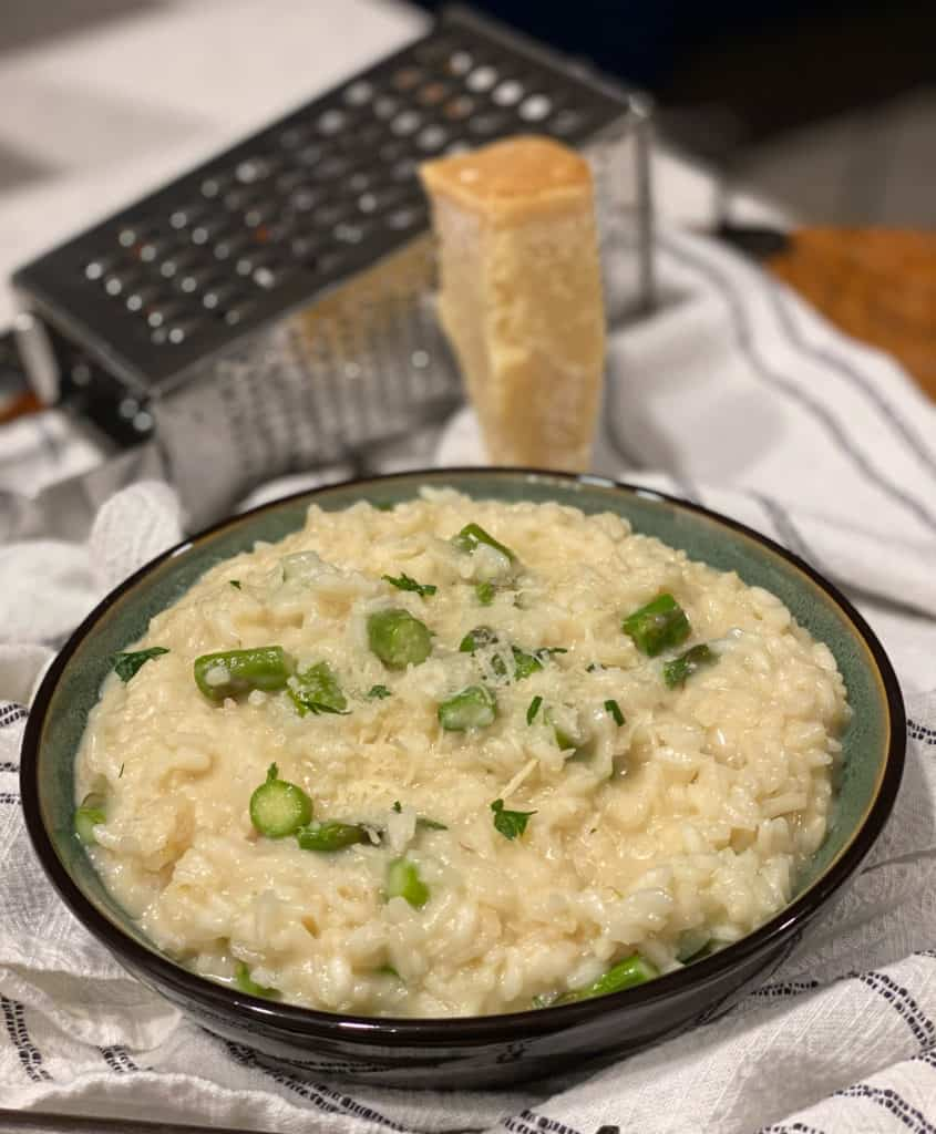 A green bowl filled with creamy Parmesan risotto with asparagus tips