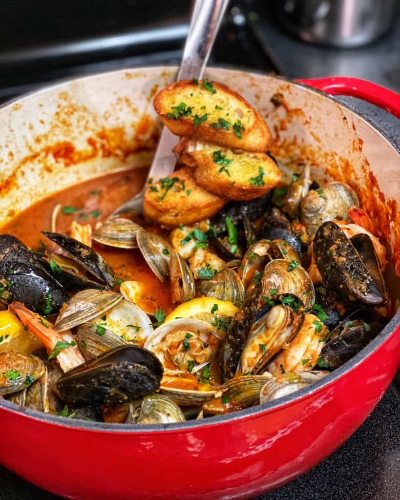 a red pot of seafood stew - cioppino