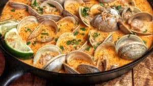 a cast iron pan full of red curry clams