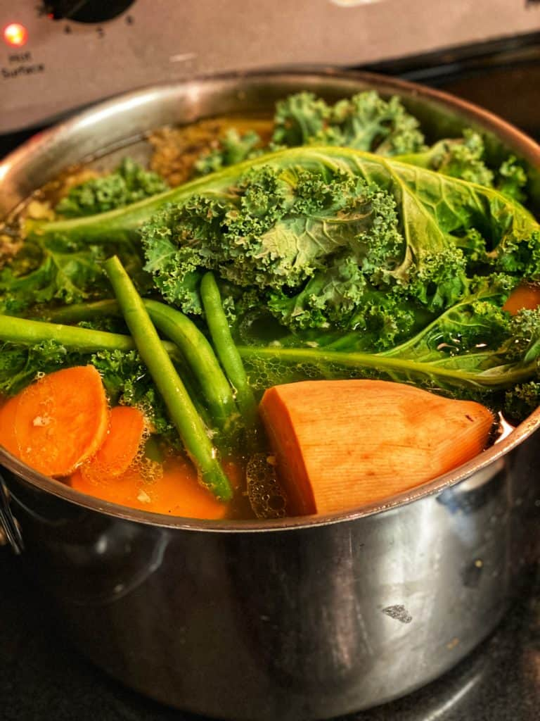 chicken bones and vegetables in a stock pot