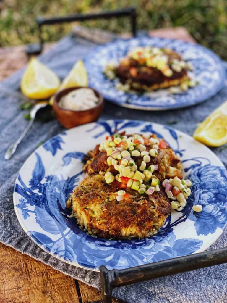 two crab cakes on two blue plate topped with corn salsa