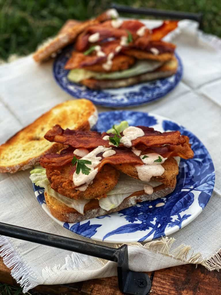 two fried green tomato bacon, lettuce and tomato sandwiches on blue floral plates