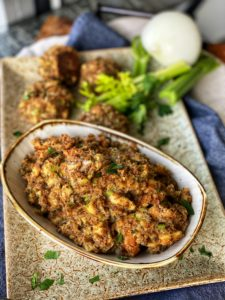 sausage stuffing in a bowl with sausage stuffing balls surrounding the plate