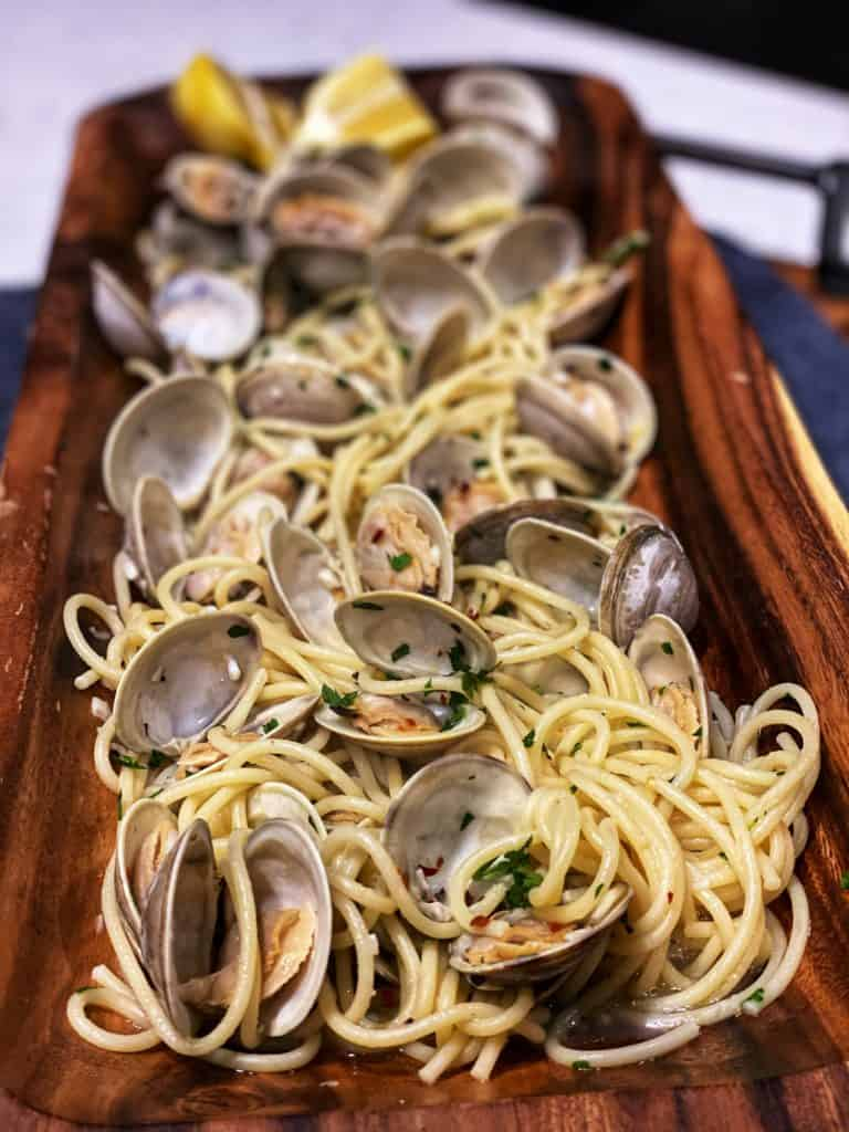 a long wooden bowl full of spaghetti with clams