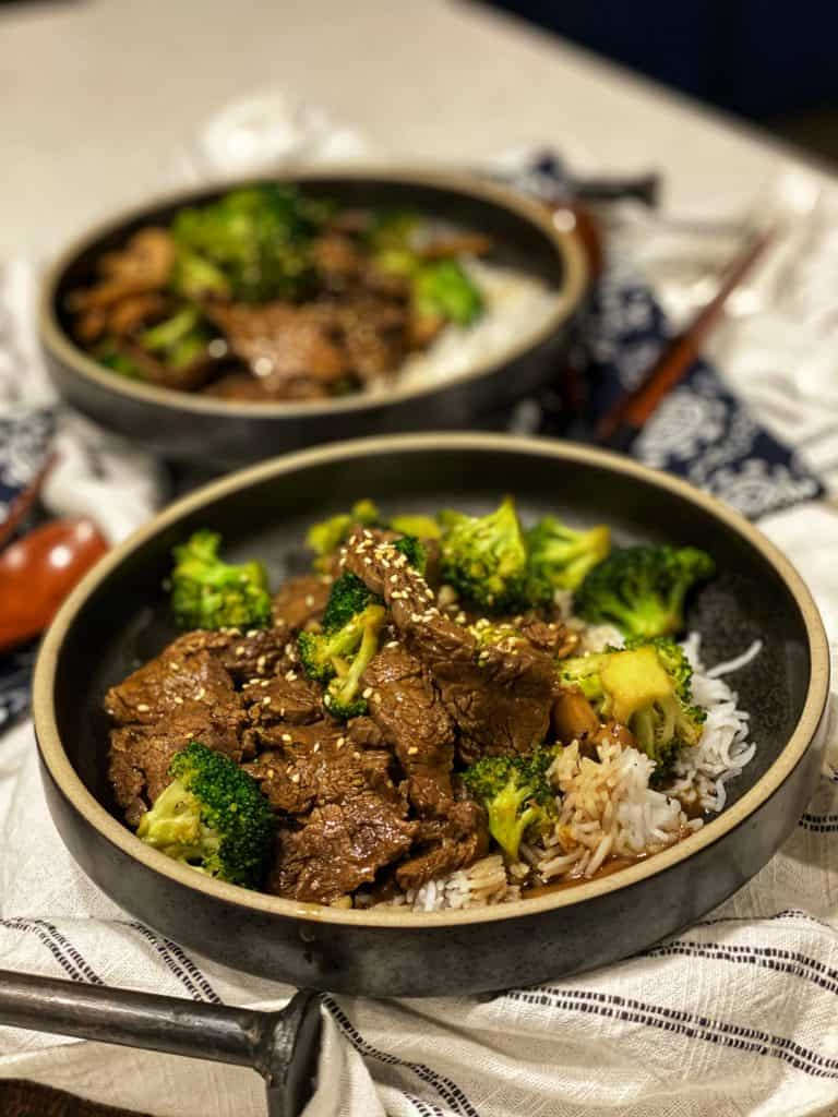 two black bowls filled with beef and broccoli over rice