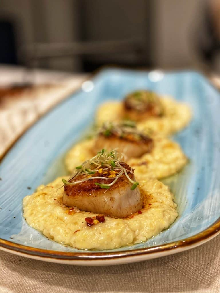 three seared scallops on a bed of corn purée topped with hot chili oil and clover sprouts on a blue plate