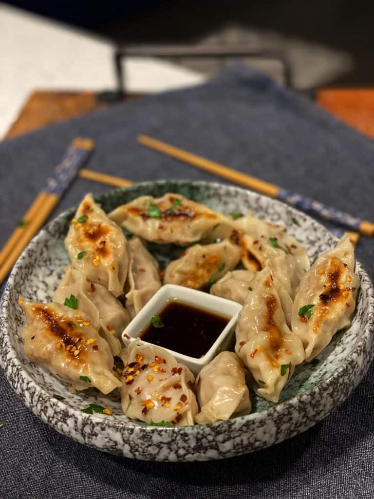 shrimp and pork gyozas in a blue marbled bowl with a small white square bowl of dipping sauce in the middle