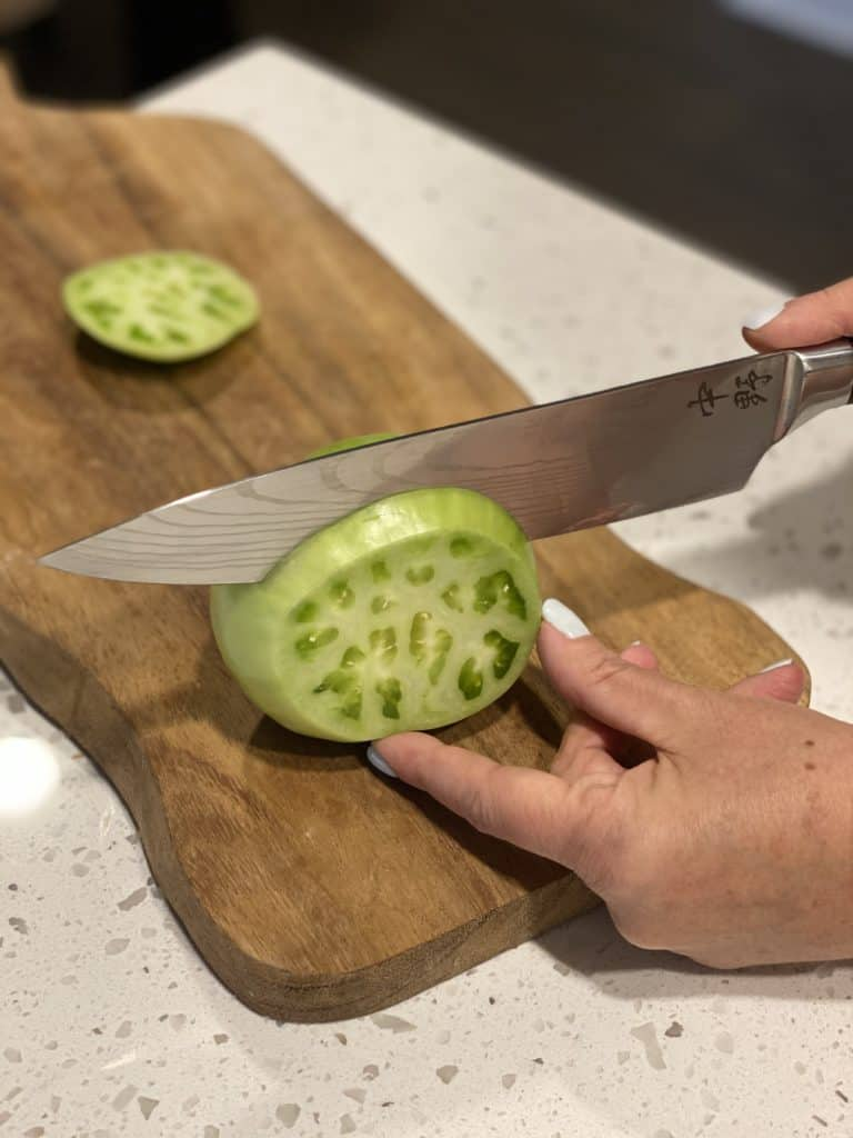 slicing up a green tomato on a wooden cutting board