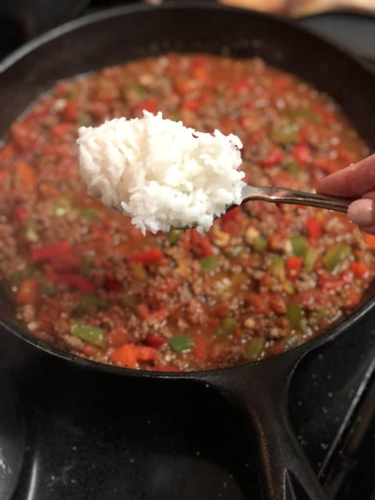 adding white rice to spanish rice mixture